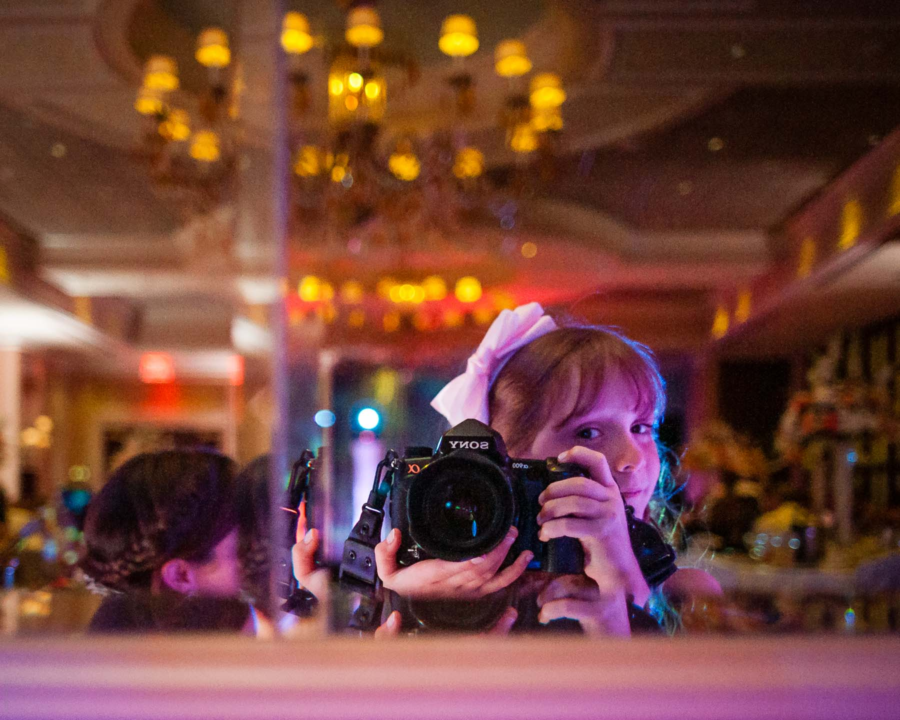 7 year old girl takes a self-portrait at a wedding with a full-frame DSLR Sony A900